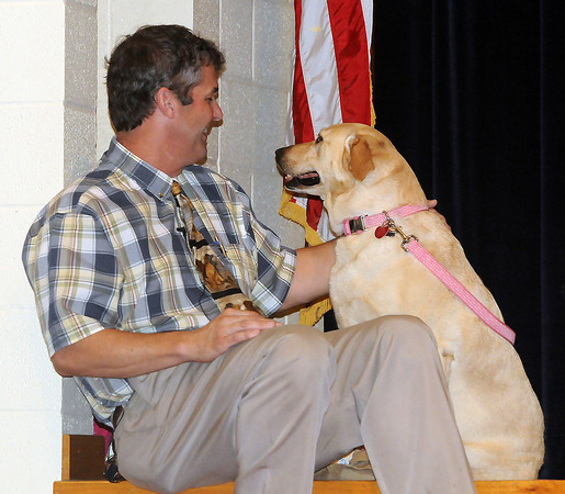 Norman veteranarian Dr. John Otto sits with therapy dog Sunshine Monday, May 21, 2012, during an assembly at Wahington Elementary School in which teacher and Sunshine owner Amber Bui announced that the dog would be used in Washington classrooms next year. Jerry Laizure/The Transcript