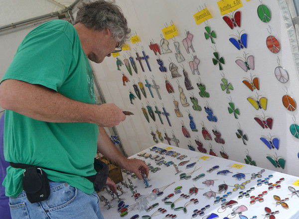 Walter Reif sets up his booth Friday afternoon in anticipation of the May Fair Arts Festival which will be at Andrews Park all day today.<br /> Kyle Phillips/The Transcript