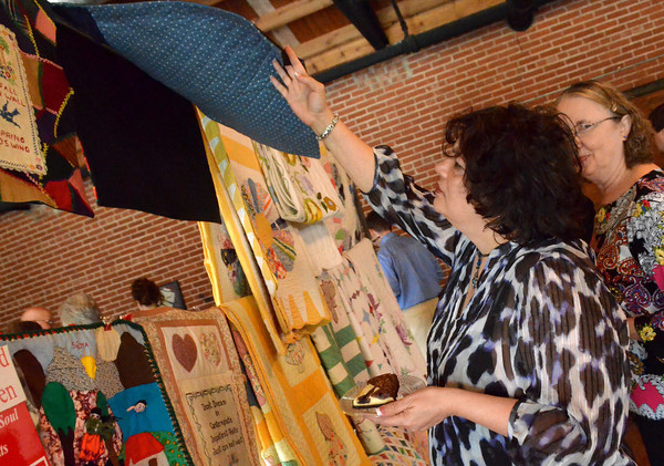 Cheryl DeLay looks at quilts that are for sale at Mission Norman's fundraising event at the Hall at Old Town Plaza Thursday evening.  The organization is holdong the first annual event in order to raise money for Mission Norman.  The quilts for the event were donated by Judy Howard.<br /> Kyle Phillips/The Transcript