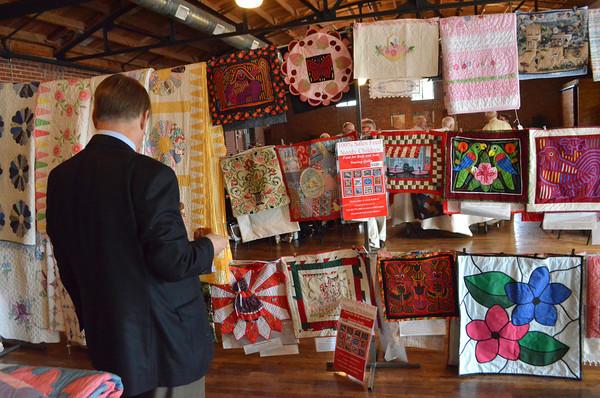Harvey Hill looks at quilts that are for sale at Mission Norman's fundraising event at the Hall at Old Town Plaza Thursday evening.  The organization is holdong the first annual event in order to raise money for Mission Norman.  The quilts for the event were donated by Judy Howard.<br /> Kyle Phillips/The Transcript