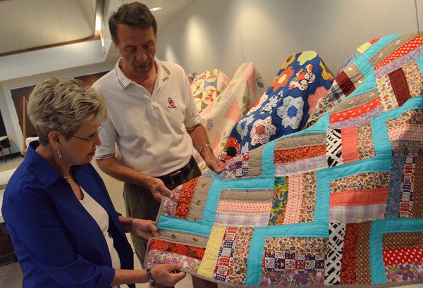 Marilynn Meier, left, and Mike Kertok look at a quilt made by Kortek's mother, who passed in March,  that is on display at First Christian Church Friday afternoon.  Kurtok says after the quilts are taken off display he will disperse them amoungst family members who want them.<br /> Kyle Phillips/The Transcript