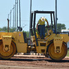 A worker keeps an eye on his line as he drives a steamroller over freshly set asphalt at the Cleveland County Fairgrounds Wednesday afternoon.  The project, which is a full county project, with the City of Norman helping with the asphalt portion, should be complete by this weekend, according to Cleveland County Commissioner Rod Cleveland.