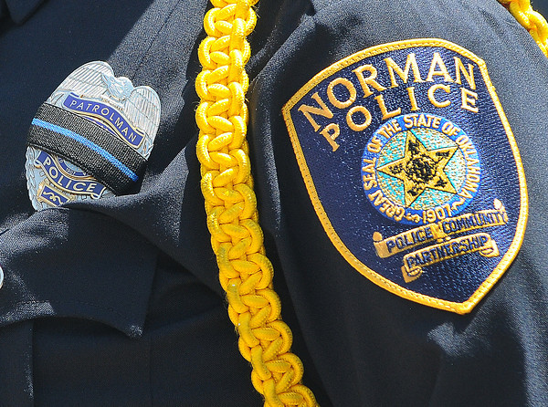 Area law enforcement officers wore black ribbons on their badges during the 2012 Law Enforcement Memorial Service at the fallen officer memorial in front of the Norman Police Department. Photo by Jerry Laizure