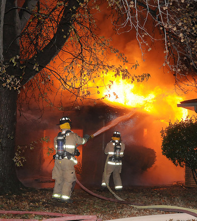 Norman firefighters attack a blazing garage at an early morning house fire Saturday Dec. 17, 2011, at 1316 Sunset Drive. The house was fully involved when firefighters arrived at the house around 12:15 a.m.  Photo by Jerry Laizure