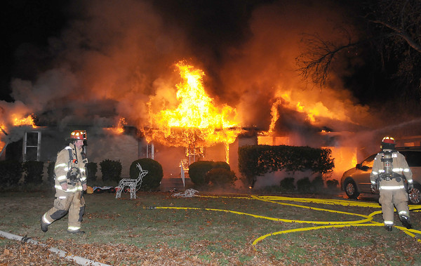 Norman firefighters prepare to attack an early morning house fire Saturday Dec. 17, 2011, at 1316 Sunset Drive. The house was fully involved when firefighters arrived at the house around 12:15 a.m.  Photo by Jerry Laizure