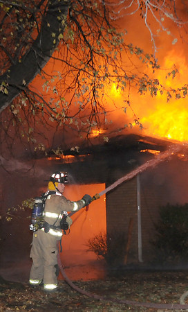 A Norman firefighter attacks a blazing garage at an early morning house fire Saturday Dec. 17, 2011, at 1316 Sunset Drive. The house was fully involved when firefighters arrived at the house around 12:15 a.m.  Photo by Jerry Laizure