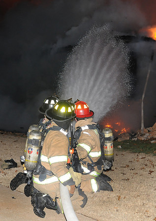 Norman firefighters attack an early morning house fire Saturday Dec. 17, 2011, at 1316 Sunset Drive. The house was fully involved when firefighters arrived at the house around 12:15 a.m.  Photo by Jerry Laizure