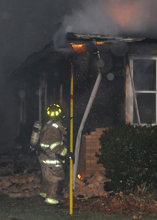 A Norman firefighter exposes hotspots Saturday Dec. 17, 2011, at an early morning house fire at 1316 Sunset Drive. The house was fully involved when firefighters arrived at the house around 12:15 a.m. Deputy chief described the fire as stubborn as it took firefighters about three hours to extinguish. Photo by Jerry Laizure