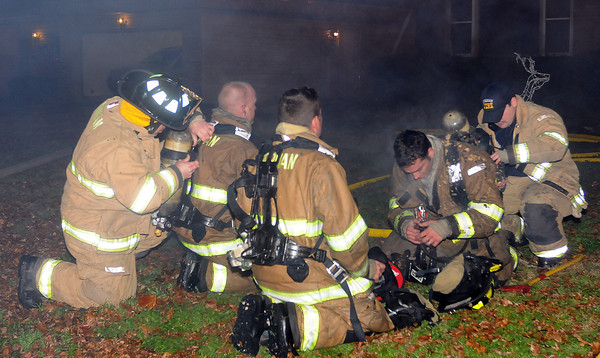 Norman firefighters get fresh airpacks Saturday Dec. 17, 2011, while fighting a fire at 1316 Sunset Drive. The house was fully involved when firefighters arrived at the house around 12:15 a.m.  Photo by Jerry Laizure