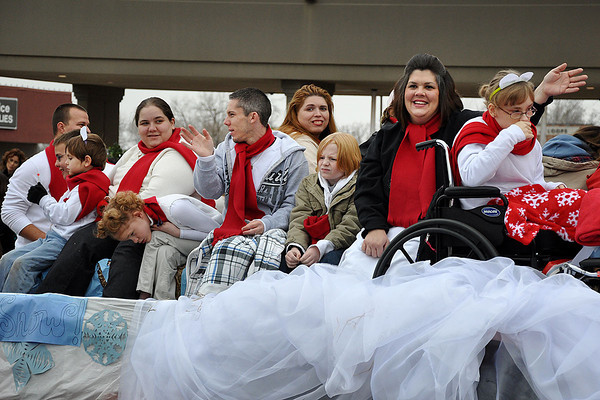 Supporters and members of the J.D. McCarty Center wave at parade goers during the Norman Christmas Parade Saturday morning. Julie Bragg/ The Transcript
