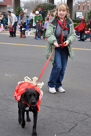 Supporters of the Top Dog Pet Resort walk during the Norman Christmas Parade with their canine companion. Julie Bragg/ For the Transcript