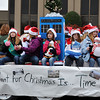 Girl Scout troop 671 wave and pass out candy to parade goers during the Norman Christmas Parade on Saturday. Julie Bragg/ For the Transcript