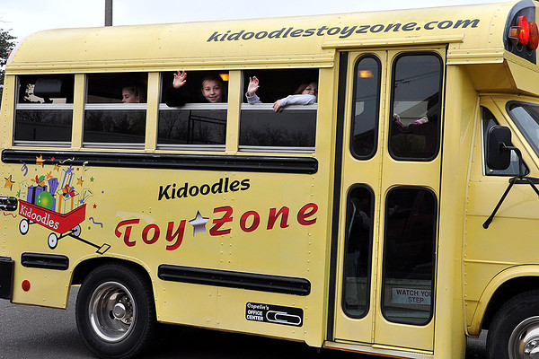 Children wave from inside the Kidoodles bus during the Norman Christmas Parade on Saturday. Julie Bragg/ For the Transcript