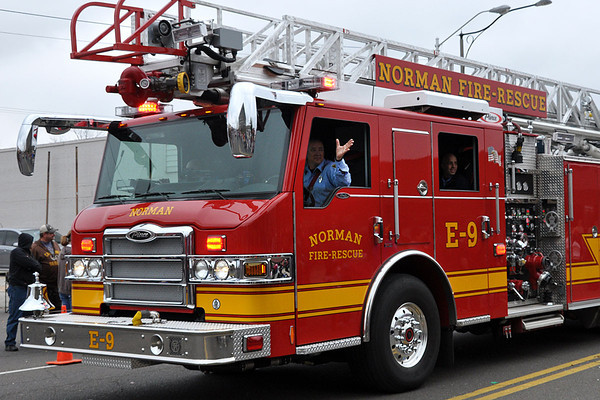 Firefighters from the Norman Fire Department drive in their fire engine during the Norman Christmas Parade on Saturday. Julie Bragg/ For the Transcript