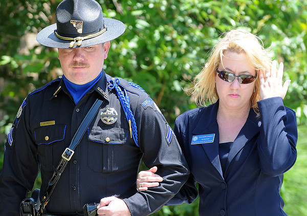 Cleveland County deputy Michael Finley escorts Sharri Dailey, secretary of the Oklahoma State FOP Auxillary after she laid a rose  at the fallen officer memorial in front of the Norman Police Department during the 2012 Law Enforcement Memorial Service. Photo by Jerry Laizure