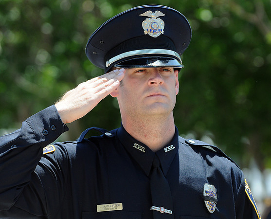 Norman police officer Lee McWhorter salutes during the singing of the National Anthem Friday, May 18, 2012, during the 2012 Law Enforcement Memorial Service at the fallen officer memorial in front of the Norman Police Department. Photo by Jerry Laizure
