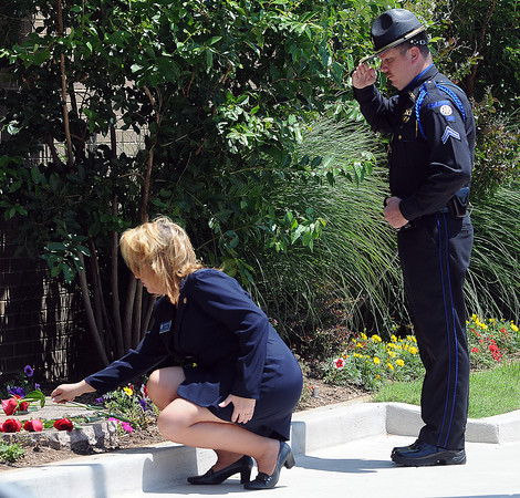 Cleveland County deputy Michael Finley salutes while Sharri Dailey, secretary of the Oklahoma State FOP Auxillary lays a rose at the fallen officer memorial in front of the Norman Police Department during the 2012 Law Enforcement Memorial Service. Photo by Jerry Laizure