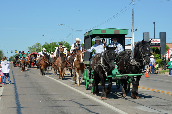 """The Wagon train rolls down Main Street Saturday morning during Norman's '89er Day Parade.  The annual parade marks celebrates the anniversary of the Great Land Run of 1889 which opened the """"Unassigned Lands"""" in central Oklahoma for settlement.<br /> Transcript Photo by Kyle Phillip"""