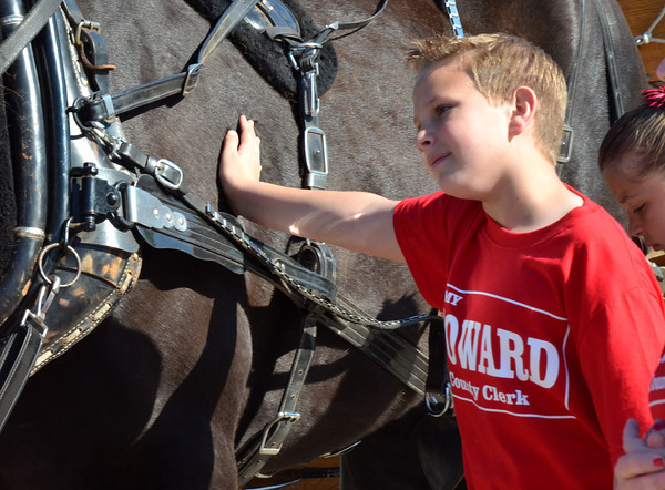 """Carson Howlett, 10, pets a horse before the start of the '89er Day Parade Saturday morning. The parade celebrates the anniversary of the Great Land Run of 1889 which opened the """"Unassigned Lands"""" in central Oklahoma for settlement.<br /> Transcript Photo by Kyle Phillips"""