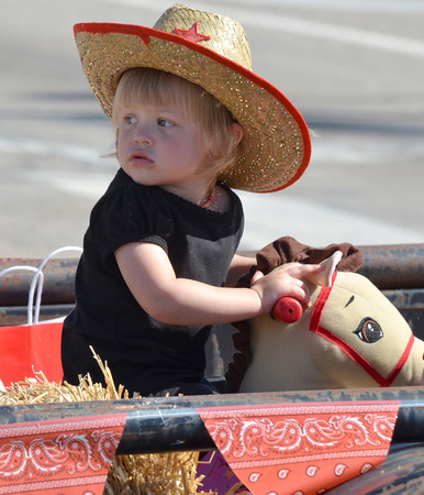 Chloe Williams, 2, sits on a toy horse as she rides on a float during Saturday's '89er Day Parade.  The parade, an annual celebration of the Great Land Run of 1889, started at Norman High School and ended at Crawford Avenue.<br /> Transcript Photo by Kyle Phillips
