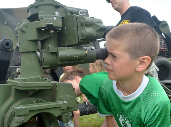 Will Clements, 8, looks through the scope of a 105 mm howitzer that was on display at the Touch a Truck event Staurday morning at the Cleveland County Fairgrounds.  Many vehicles were on display, including fire trucks, police cruisers and service trucks used for delivery and fright,  for children to climb into and look around.  <br /> Transcript Photo by Kyle Phillips