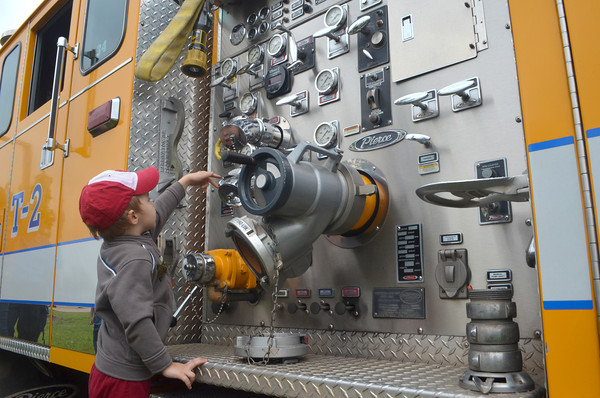 Greyson Vidrine touchs dials that control water flow on a Norman Fire Truck Saturday morning at the 8th annual Touch a Truck event at the Cleveland County Fairgrounds.  Children were also can tour the a  helicopter and vehicles from the Oklahoma Highway Patrol.<br /> Transcript Photo by Kyle Phillips