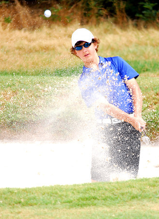 Travis McInroe watches his ball as he chips out of a sand trap Tuesday afternoon during the Sooner Junior All-Stars golf tournament at the Jimmie Austin OU Golf Club.  To see more photos from the tournament visit our photo page at: photos.normantranscript.com/Eventphotos.<br /> Kyle Phillips/The Transcript