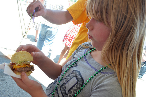 Brittney Blue checks out the burger she got from the Holiday Inn team Saturday at the 2nd Annual Battle of the Burger at Marc Heitz Chevrolet.<br /> Kyle Phillips