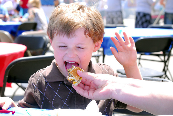 Cole Carney, 4, takes a bite out of a burger during the 2nd Annual Battle of the Burger Saturday afternoon at Marc Heitz Chevrolet.  Money raised from the event will benefit OK Kids Korrall, a Toby Keith Foundation project. <br /> Kyle Phillips/The Transcript
