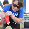 Julie Burton prepares a green chili burger with chipotle ranch sauce for the judges Saturday at the 2nd Annual Battle of the Burger at Marc Heitz Chevrolet.<br /> Kyle Phillips/The Transcript