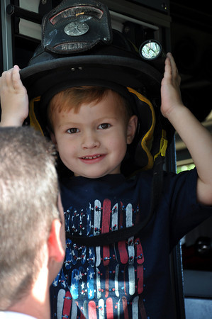 Caden Taylor, age 3, son of Tya Taylor of Norman, tries on Sgt. Eric Means' helmet at the Brookhaven Fourth of July festivities on Wednesday. Julie Bragg/ The Transcript