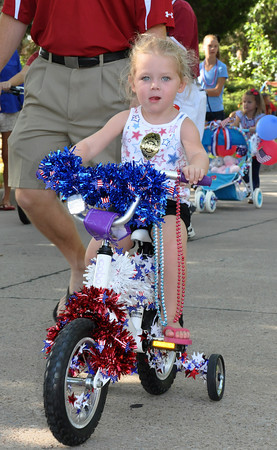 Elle Morgan, age 3, daughter of Tim Morgan, rides her decorated bicycle in the parade down Brookhaven Boulevard on Wednesday. Julie Bragg/ The Transcript
