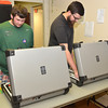 Kasey Wilson, left, and Trey Gaylord close down ballot machines Tuesday night as they are brought in from the precincts around Cleveland County.<br /> Kyle Phillips/The Transcript