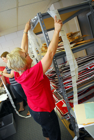 Deedee Calhoun hangs up election papers as she and others organize the paperwork at the Cleveland County Election Board Tuesday evening.<br /> Kyle Phillips/The Transcript