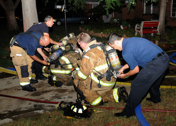 Norman firefighters get frsh air bottles while battling a house fire Tuesday, June 26, 2012, in the 1000 block of Leslie Lane.  Jerry Laizure / The Transcript
