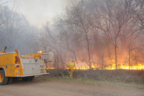 Norman fireifighters attempt to stop a wildfire from jumping Bounbonnais Creek Road in far eastern Cleveland County.