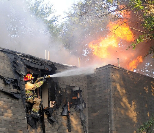 A Norman firefighter fights a blaze in a duplex in the 600 block of Sinclair Drive, Thursday, June 14, 2012. Four engine companies and one truck company responded to the blaze along with two EMSStat units. Norman police units provided traffic control. The fire marshal said it was too early to comment on the source of the fire. Jerry Laizure / The Transcript