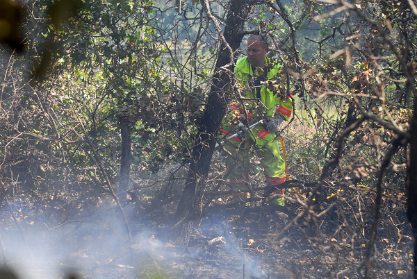 A Little Axe firefighter sprays down hot spots in a field along 108th Ave. NE after a grass fire broke out in the area Wednesday afternoon.<br /> Kyle Phillips/The Transcript