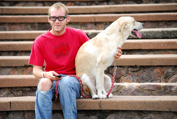 Matthew Taylor and his dog Trunker sit and listen to the Beau Mansfield Trio Sunday afternoon at Andrews Park during Groovefest.<br /> Groovefest is the longest running human rights festival.<br /> Kyle Phillips/The Transcript