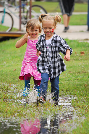 Cleo Lyon, left, and Skyler Allen play in a rain puddle at  Andrews Park Sunday afternoon.  Norman has seen an abundent amount of rain in the past few days, which is needed to get rid of the drought that plagued Oklahoma over the summer.<br /> Kyle Phillips/The Transcript