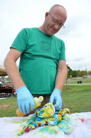 Chris Webb works on his tie dye shirt Sunday afternoon during Groovefest at Andrews Park.  The festival included live music,  a variety of vendors and booths, as well as free arts activities for all ages, provided by Scissortail School of Art.<br /> Kyle Phillips/The Transcript