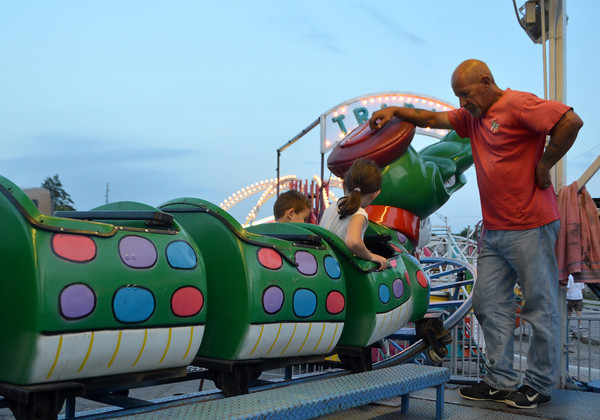 Carnival worker Pops Ferguson makes sure kids get safely off a ride Thursday  at the Lions Club Carnival near Coach's on Main Street.  The carnival will run until 6 p.m. on Sunday<br /> Transcript Photo by Kyle Phillips