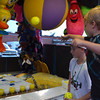 Kole Sharp tries to launch a ball into a cup and win a prize at a game booth at the Lions Club Carnival Thursday evening.<br /> Transcript Photo by Kyle Phillips