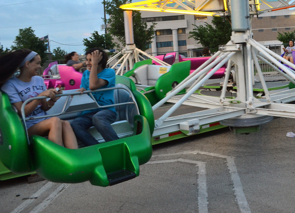 Kaitlin Pisek, left, and Tristen Trujillo ride the Sizzler  at the Lions Club Carnival near Coach's on Main Street.  The carnival will run until 6 p.m. on Sunday<br /> Transcript Photo by Kyle Phillips