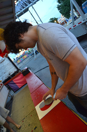 Kale Littlefield tries to win a game by covering all of the red cirlce with other smaller circles to Thursday at a booth at the Lions Club Carnival near Coach's on Main Street.  The carnival will run until 6 p.m. on Sunday<br /> Transcript Photo by Kyle Phillips