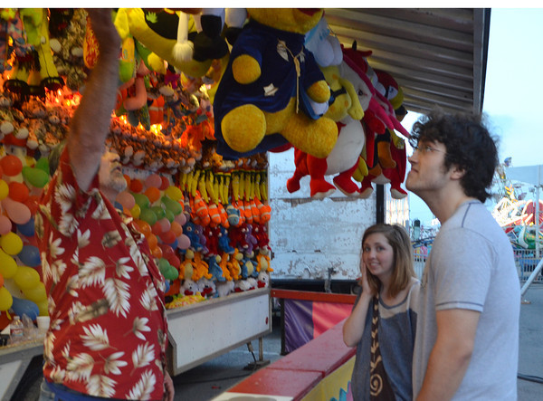 Kale Littlefield looks at all the prized he could win Thursday at a game  booth at the Lions Club Carnival near Coach's on Main Street.  The carnival will run until 6 p.m. on Sunday<br /> Transcript Photo by Kyle Phillips