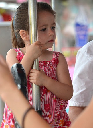 Ava Armstrong, 3,  holds on as she rides the Carousel Saturday afternoon at the Lions Club Carnival.<br /> Transcript Photo by Kyle Phillips