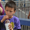 Sam Wang-Koenigsberg drinks the juice from his grape snowcone that he bought from a food booth at the Lions Club Carnival Saturday afternoon.<br /> The Carnival will continue today until 6 p.m..<br /> Transcript Photo by Kyle Phillips