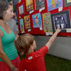 Levi Chaffin, right, shows his mom, Kylee, a painting in the children's art area tent at the May Fair Saturday afternoon at Andrews Park.<br /> Kyle Phillips/The Transcript