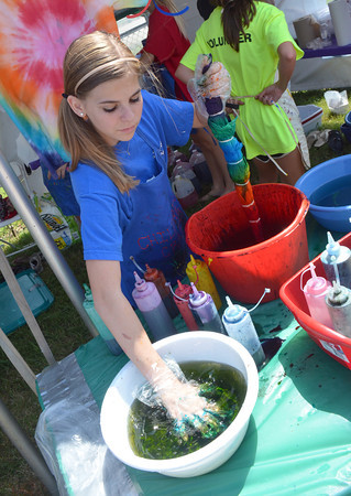 Jillian Uhles dips her hand in coloring as she makes her own tie dye shirt at the adventures in art tent at the May Fair Saturday afternoon at Andrews Park.<br /> Kyle Phillips/The Transcript